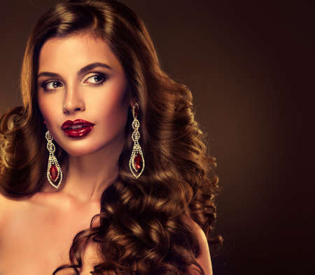 glamour makeup: Beautiful girl model with long brown curled hair with large necklace