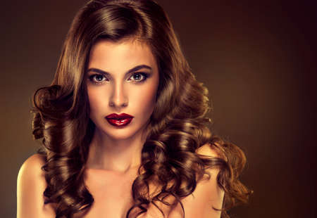 Beautiful girl model with long brown curled hair with large necklace