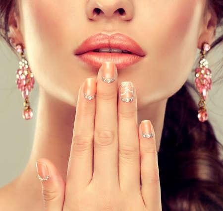 volti: Trucco per occhi e labbra, eyeliner e rossetto corallo. Archivio Fotografico