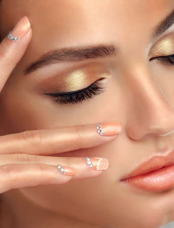 finger tip: Makeup for eyes and lips, eyeliner and coral lipstick. Stock Photo