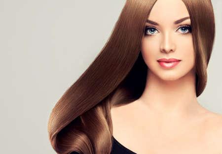光沢のある茶色の長いストレート髪の女の子モデルの美しさ