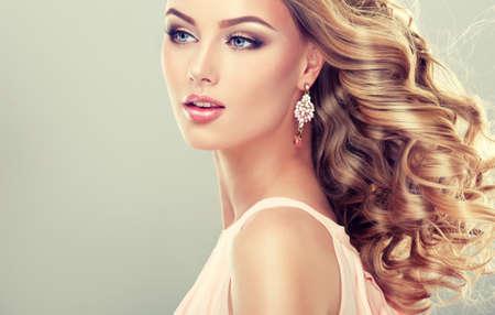 時尚: 微笑美麗的女孩淺棕色的頭髮有一個優雅的髮型 版權商用圖片