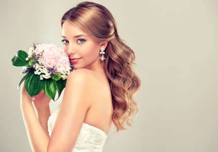 brides: Girl bride in wedding dress with elegant hairstyle and with a wedding bouquet Stock Photo
