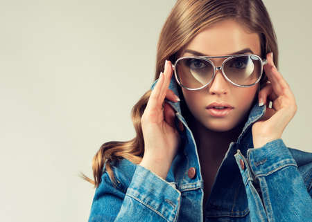 Beautiful girl model in denim jacket and sunglasses