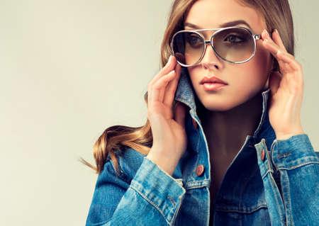 mezclilla: Modelo de la muchacha hermosa en la chaqueta de mezclilla y gafas de sol