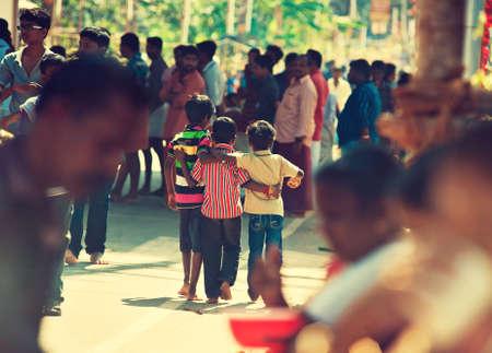 jardin de ni�os: India. Kerala. Tres j�venes amigos caminando a trav�s de multitud. Editorial