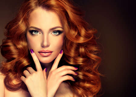 Girl model with long curly red hair. Trendy image red head woman and purple nails