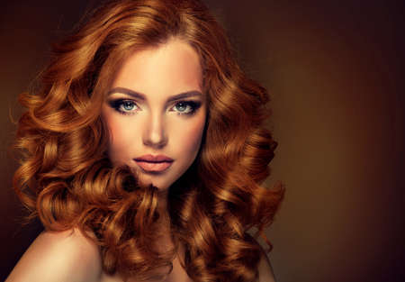 Girl model with long curly red hair. Trendy image red head woman. Archivio Fotografico