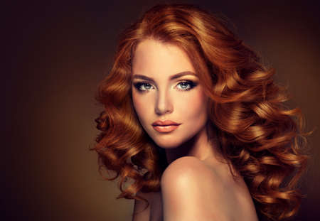 Girl model with long curly red hair. Trendy image of a red head woman Archivio Fotografico