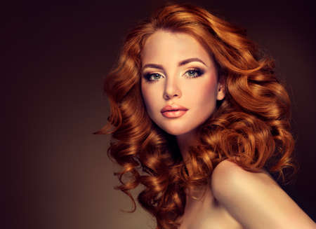 Girl model with long curly red hair. Trendy image of a red head woman 免版税图像