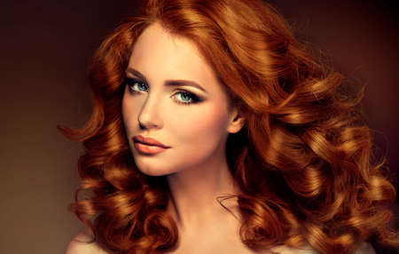 long curly hair: Girl model with long curly red hair. Trendy image of a red head woman Stock Photo