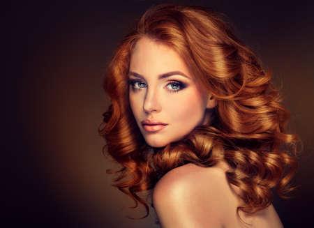 長い巻き毛の赤い髪の女の子モデル。トレンディーなイメージの赤の頭の女性。