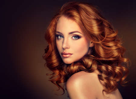 Girl model with long curly red hair. Trendy image red head woman. Stockfoto