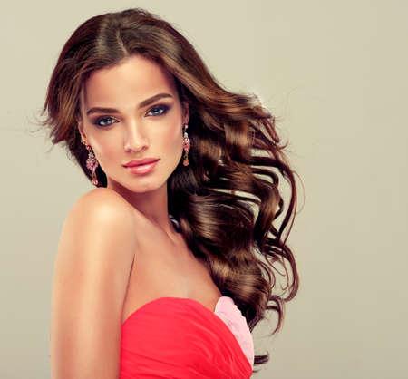 Mooi model brunette met lang gekruld haar in koraal jurk Stockfoto