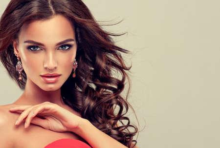 サンゴの長いカールした髪とブルネットの美しいモデルのドレスします。