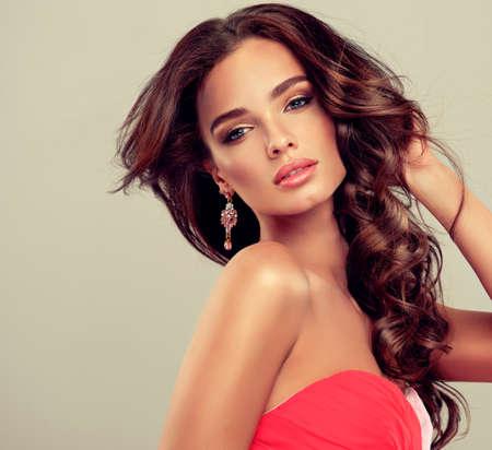 ojos hermosos: Bella modelo morena con el pelo rizado largo vestido coral