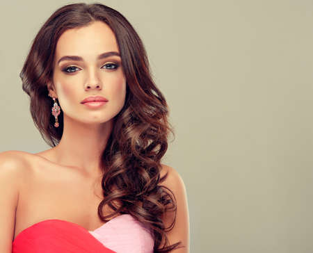 bang: Beautiful model brunette with long curled hair in coral dress Stock Photo
