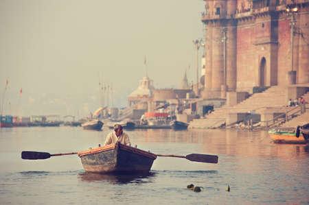 varanasi: Varanasi. Indian boatman driving own boat by the Ganges river, along Varanasi ghats. Editorial