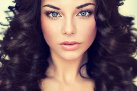 hair curl: Beautiful girl model with long black curled hair Stock Photo