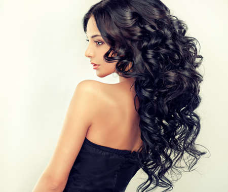 Beautiful girl model with long black curled hair Stockfoto