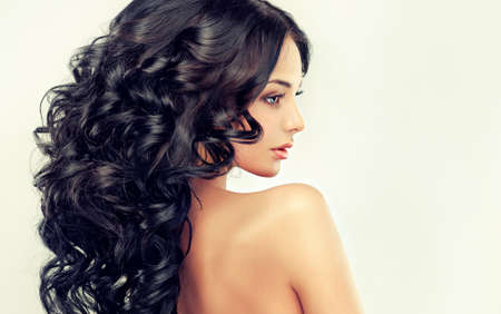 Beautiful girl model with long black curled hair Stock Photo