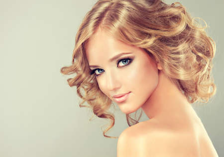 perm: Pretty blonde girl with hairstyle curled hair .Hairstyle medium length