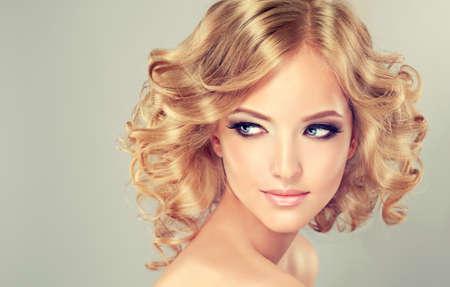 secador de pelo: Muchacha bastante rubia con el peinado rizado pelo .Hairstyle longitud media