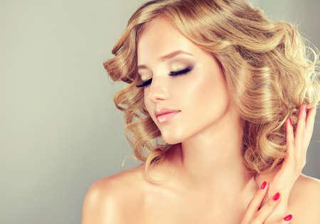 secador de pelo: Muchacha bastante rubia con el peinado rizado pelo estilo de la moda .Luxury, manicura.