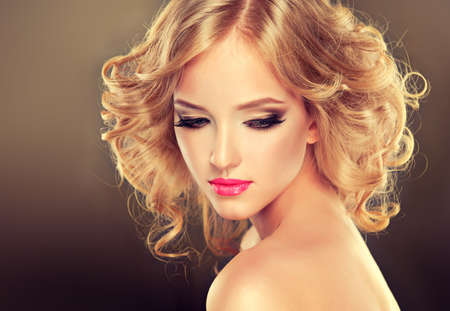 medium closeup: Pretty blonde girl with hairstyle curled hair .Luxury fashion style.