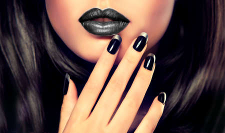 Beautiful model brunette shows black and silver French manicure on nails. Imagens
