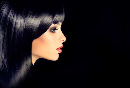 The girl in profile with black straight shiny hair and bangs . Model brunette with hairstyle of the care. Luxury fashion style, hair, cosmetics ,make-up Standard-Bild