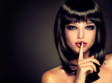 secador de pelo: La niña con un secreto. Modelo morena con el peinado de la atención. Pelo negro y una manicura negro en el estilo de la moda nails.Luxury, las uñas de manicura, cosmética, maquillaje