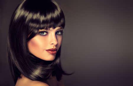 Het meisje in profiel met zwart recht glanzend haar en een pony. Model brunette met kapsel van de zorg. Luxe mode-stijl, haar, cosmetica, make-up Stockfoto
