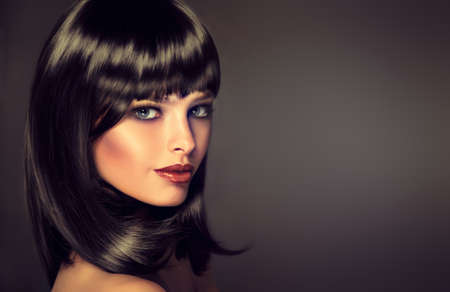 bangs: The girl in profile with black straight shiny hair and bangs . Model brunette with hairstyle of the care. Luxury fashion style, hair, cosmetics ,make-up Stock Photo