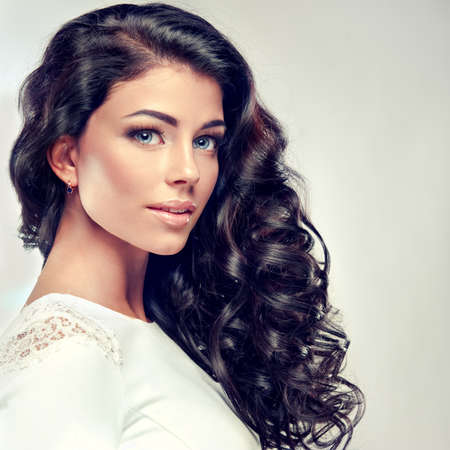 Portrait.Model brunette with long,dense curly hair in a white gown. Banque d'images