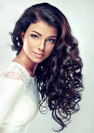 Portrait.Model brunette with long,dense curly hair in a white gown. 免版税图像