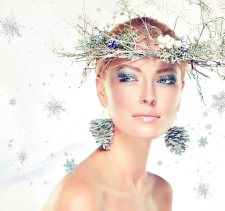 Christmas fashion model girl with snowy wreath on the head Stock Photo