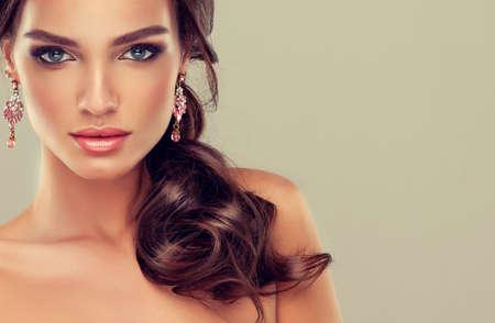 belle brune: Belle jeune fille aux cheveux brun clair avec une coiffure élégante, vague de cheveux, coiffure bouclée