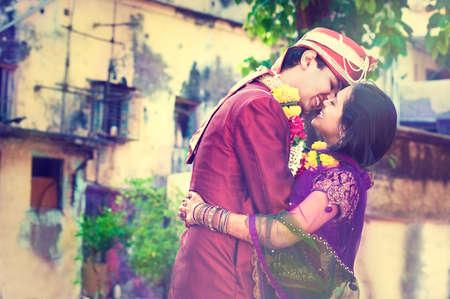 feier: Junge indische Ehepaar nach weddind Zeremonie. Junge glückliche family.Indian Bräutigam und Braut in den traditionellen Brautkleid.