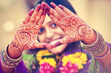 結婚式: インドの花嫁は、手の一時的な刺青の絵を示しています。インドの結婚式。
