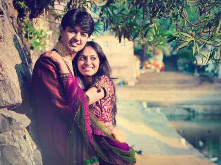 結婚式: 若いインドは、weddind 式の後カップルを結婚しました。若い幸せな家族。インドの新郎と新婦が伝統的なウェディング ドレスで。