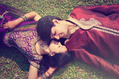 salwar: Happy Indian new married couple laying on the grass.
