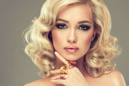 girl with rings: Beautiful girl with blonde curly hair with a big rings of precious stones on fingers Stock Photo