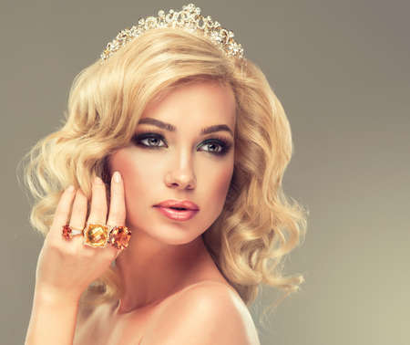 head stones: Beautiful girl with blonde curly hair with a big rings of precious stones on fingers and diadem on head.