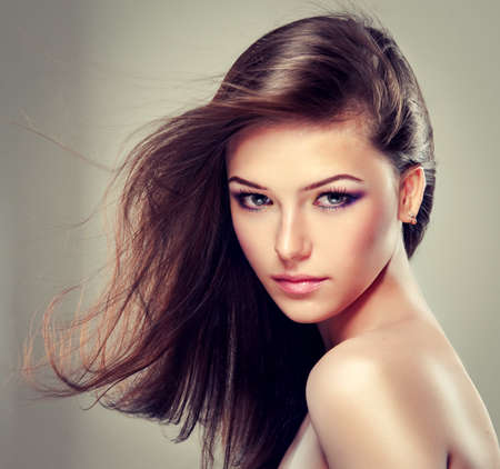 face: Brunette girl with long straight hair. Fashionable hairstyle and makeup.