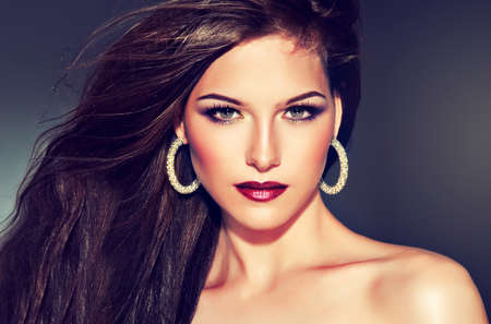 forelock: Brunette girl with long straight hair. Fashionable hairstyle and makeup.
