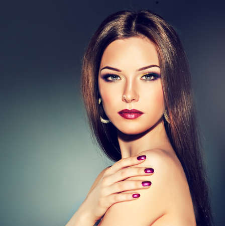 Brunette girl with long straight hair. Fashionable hairstyle and makeup.