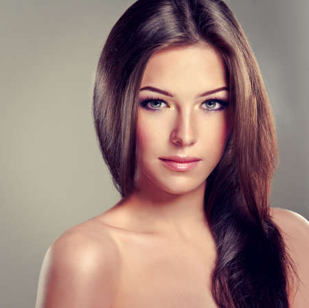 look up: Brunette girl with long straight hair. Fashionable hairstyle and makeup.