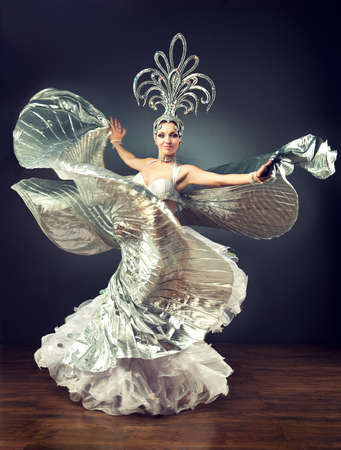 Dancing girl in the carnival costume. Expressive movement of dance.