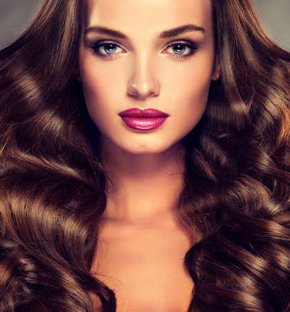 pelo largo: Modelo de Niza chica joven con densa, pelo rizado. Brillante moda maquillaje y peinados. Foto de archivo